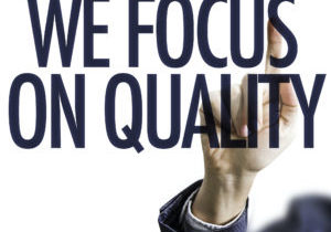 Business man pointing the text: We Focus on Quality